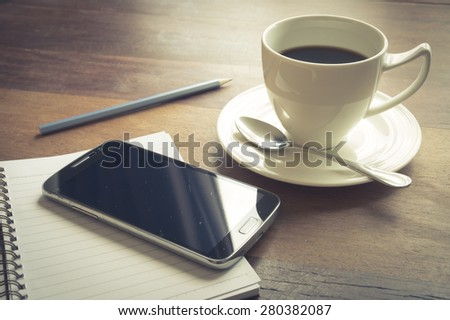 Smart phone with coffee cup,book and pencil.vintage filtered.