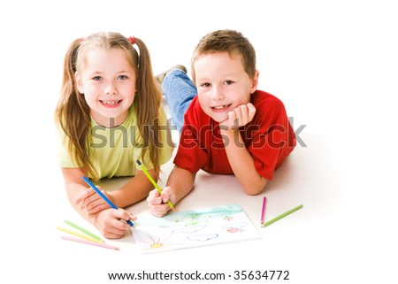 Smart schoolchildren looking at camera while drawing with colorful pencils