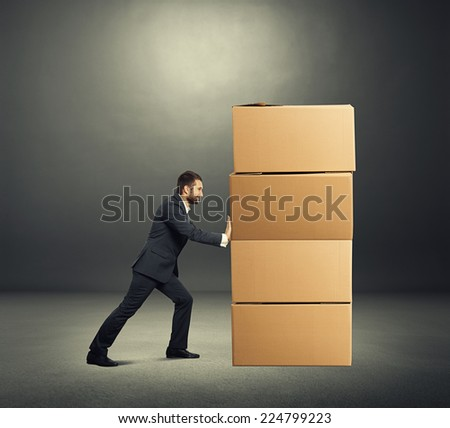 smiley businessman moving cardboard boxes. photo in the dark room