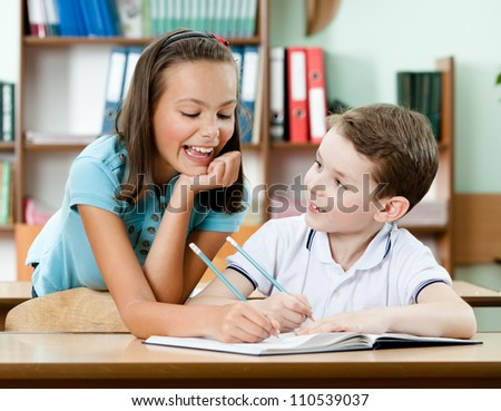Smiley schoolgirl helps to her friend to do the task
