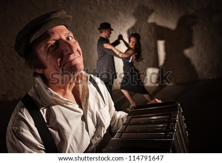 Smiling accordion player performing with dancers in the background