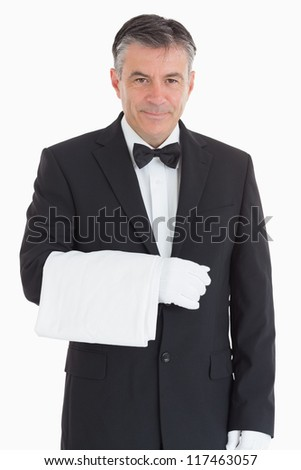 Smiling and standing waiter holding a towel in front of camera