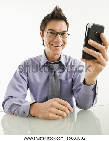 Smiling Asian businessman with his pda cellphone.