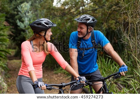 Smiling athletic couple looking face to face while riding bicycle