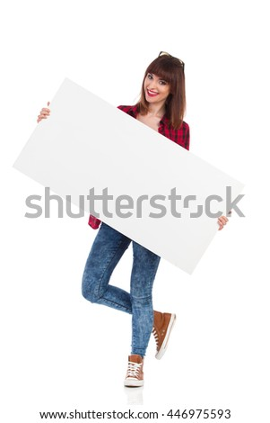 Smiling attractive woman in red lumberjack shirt, jeans and brown sneakers, standing on one leg and holding big white poster. Full length studio shot isolated on white.