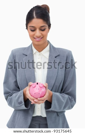 Smiling bank employee looking at piggy bank in her hands against a white background