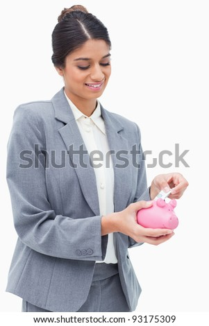 Smiling bank employee putting money into piggy bank against a white background
