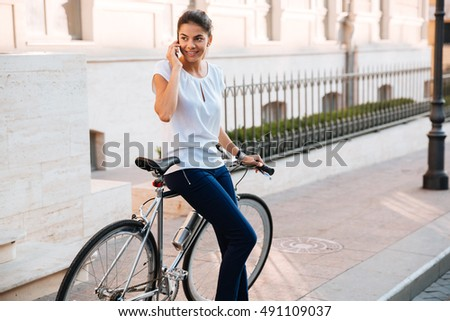 Smiling beautiful woman talking on the phone leaning on bicycle on the street