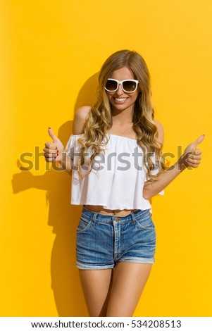 Smiling blond young woman in jeans shorts, white shirt and sunglasses showing thumbs up. Three quarter length studio shot on yellow background.
