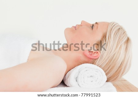 Smiling blonde woman enjoying her treatment while lying down in a Spa center