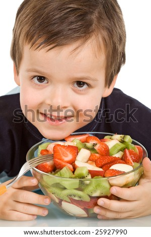 Smiling boy holding a bowl of sliced fruits - isolated, closeup