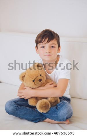 Smiling boy in a white t-shirt and blue jeans sitting on a white couch and hugging a soft toy bear.