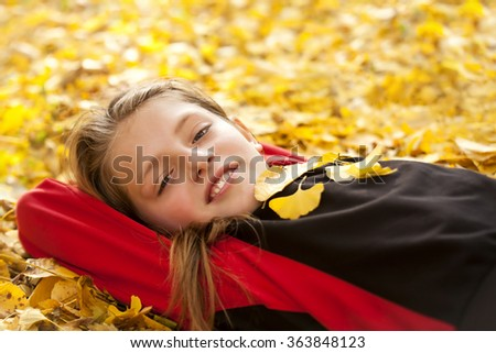 smiling boy in autumn leaves