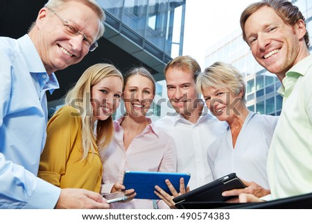 Smiling business people with tablet computer standing in a group next to the office
