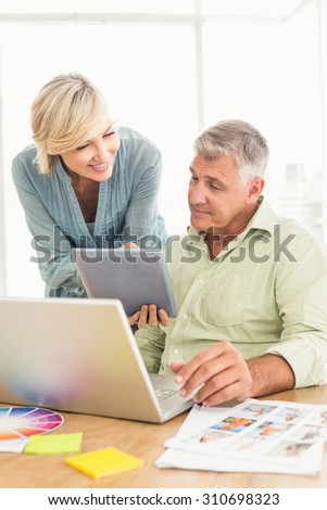 Smiling business team talking over a laptop at office