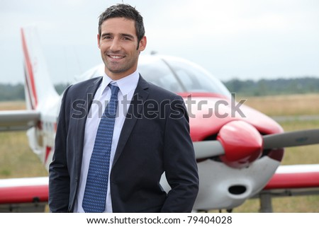 Smiling businessman standing in front of a light aircraft