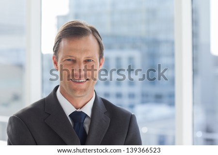 Smiling businessman standing in his office