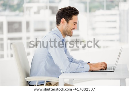 Smiling businessman working on computer in office