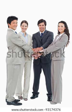 Smiling businessteam putting their hands together against a white background