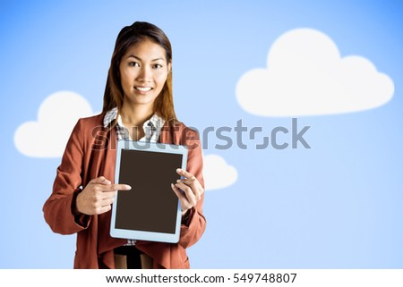 Smiling businesswoman pointing a tablet against bright blue sky with clouds