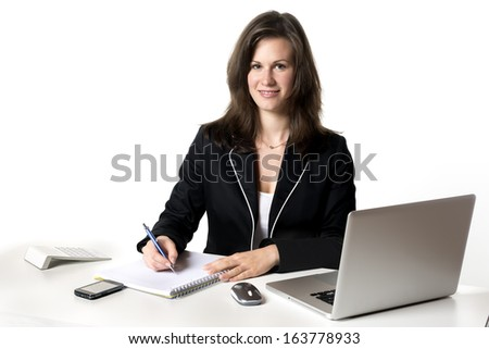 Smiling Businesswoman sitting at desk in office, writing something on a pad, isolated on white background