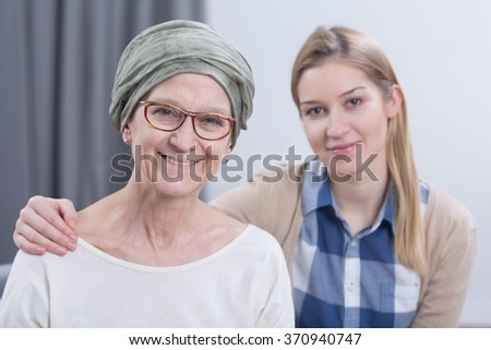 Smiling cancer woman with headscarf with young daughter