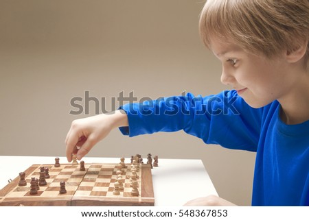 Smiling caucasian child playing a game of chess. Game, education, lifestyle concept