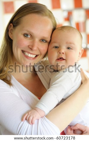 Smiling caucasian mother is holding her baby boy.