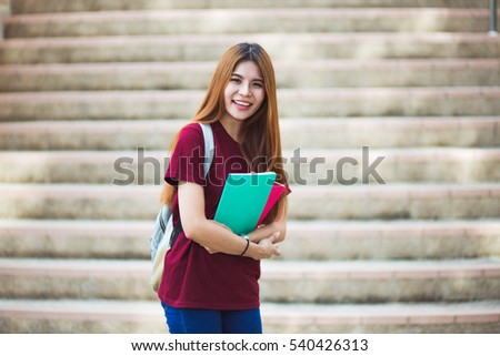 Smiling college student sitting on staircase