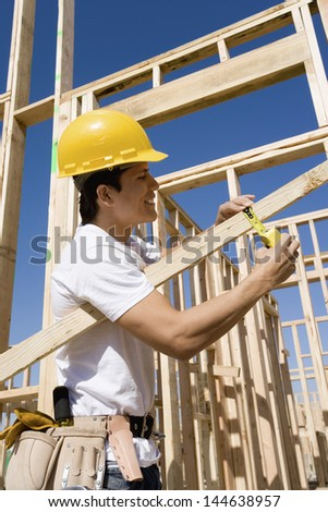 Smiling construction worker measuring timber against sky at the site