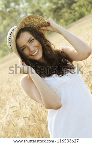 Smiling country girl , happy in a wheat field