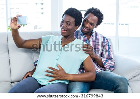 Smiling couple clicking selfie while sitting sitting on sofa at home