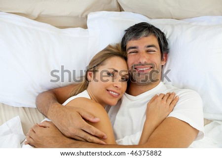 Smiling couple embracing lying in bed at home