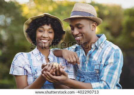 Smiling couple holding potatoes in the garden