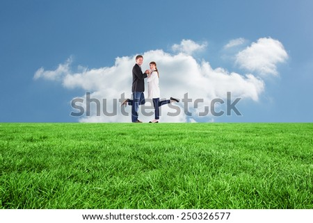 Smiling couple with raised legs against cloudy sky