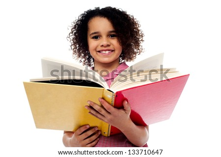 Smiling cute school girl reading a book, preparing for examinations.