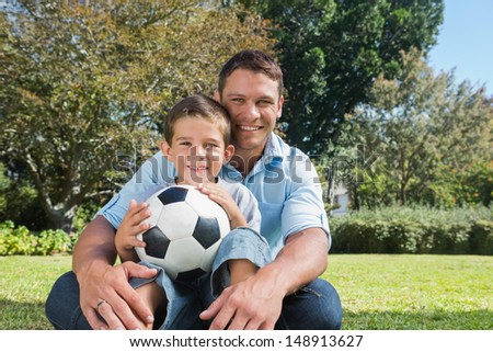 Smiling dad and son with a football in the park on sunny day