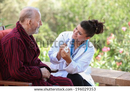 smiling Dr or nurse giving medication to senior patient.