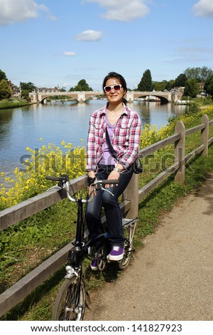 Smiling East Asian Woman Looking the Camera near the Thames River, Hampton Court Bridge in distace, with Bicycle on sunny day