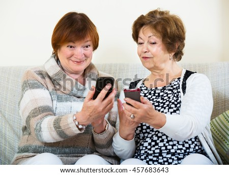 Smiling elderly friends sitting with smartphones in living room