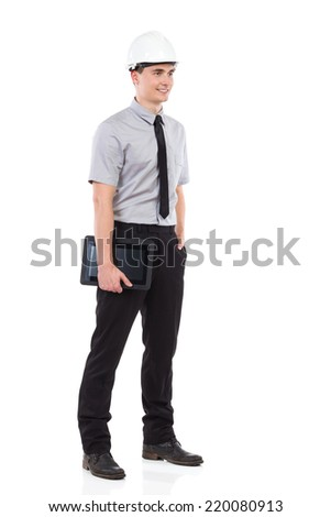 Smiling engineer posing with digital tablet and looking away. Full length studio shot isolated on white.