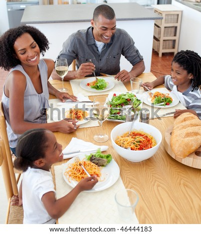 Smiling family dining together in the kitchen