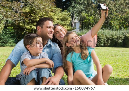 Smiling family in a park taking photos in the sunshine