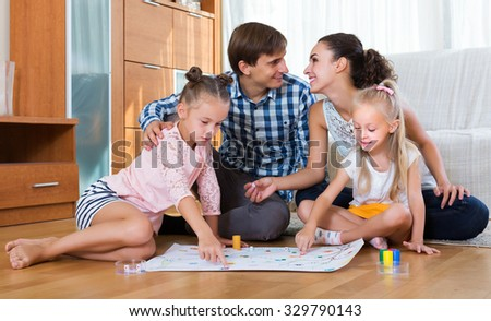 Smiling family of four playing at board game in domestic interior