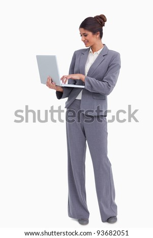 Smiling female entrepreneur working on her laptop against a white background