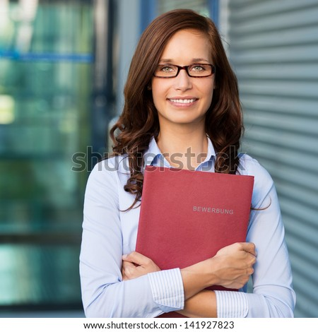 Smiling female holding a book against the blurred background
