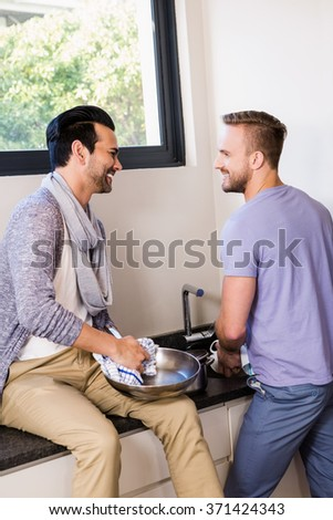 Smiling gay couple washing dishes in the kitchen