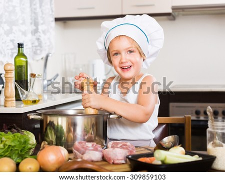 Smiling girl cooking soup at kitchen