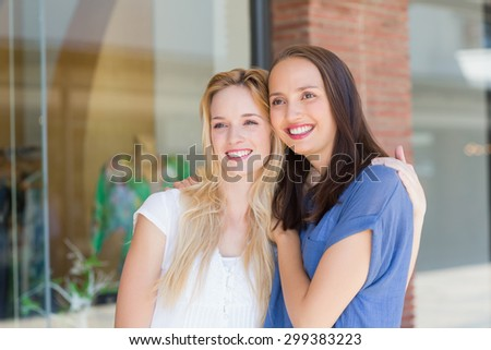 Smiling girl friends with arms around looking away