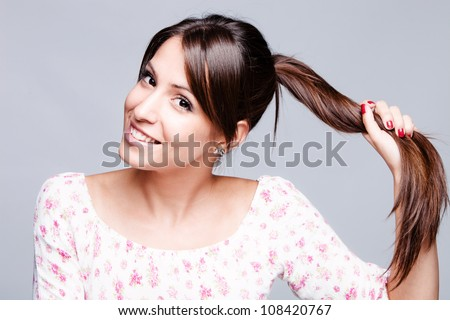 smiling girl hold her long shiny  hair in one hand studio shot
